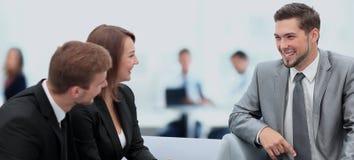 Счастливые бизнесмены говоря на встрече на офисе Стоковая Фотография RF