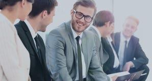 Счастливые бизнесмены говоря на встрече на офисе Стоковые Изображения