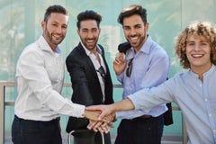Счастливые бизнесмены держа руки совместно в жесте единства Стоковое фото RF