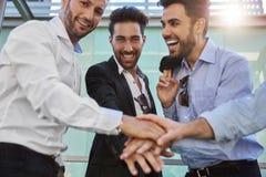 Счастливые бизнесмены держа руки совместно смеясь над Стоковое Фото