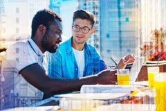 Счастливые бизнесмены обсуждая проект Стоковые Фото