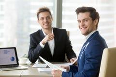 Счастливые бизнесмены представляя на столе во время встречи Стоковая Фотография