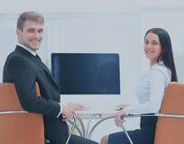 Счастливые бизнесмены смотря камеру в офисе и используя com Стоковые Изображения