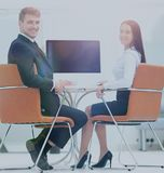 Счастливые бизнесмены смотря камеру в офисе и используя com Стоковые Фото