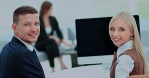Счастливые бизнесмены смотря камеру в офисе Стоковая Фотография