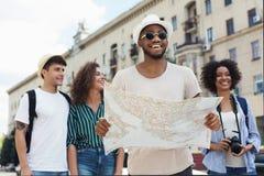 Счастливые битники используя навигацию составляют карту для того чтобы исследовать город стоковое фото