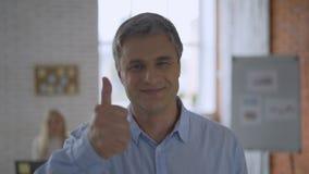 Счастливые большие пальцы руки вверх и выражение улыбки в 4K Съемка портрета статическая мужск человека в фокусе на яркой кирпичн сток-видео