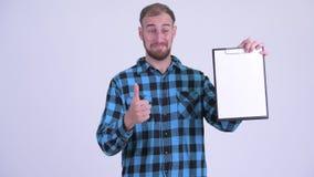 Счастливые бородатые доска сзажимом для бумаги показа человека хипстера и давать большие пальцы руки вверх сток-видео