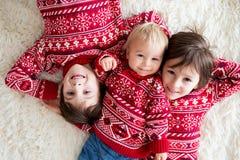 Счастливые братья, младенец и дети дошкольного возраста, обнимающ дома на белом одеяле, усмехаясь стоковые фото