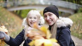 Счастливые букеты матери и дочери развевая листьев осени видеоматериал