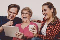 Счастливые взрослые дети с пожилой матерью на кресле стоковое фото