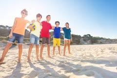 Счастливые волейболисты обнимая на суде песка стоковое изображение rf