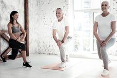 Счастливые выбытые люди тренируя и усмехаясь на фитнес-клубе Стоковое Фото