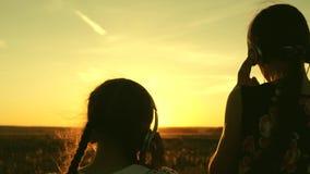 Счастливые девочка-подростки слушая музыку и танцуя в лучах красивого захода солнца в парке дети в наушниках внутри видеоматериал