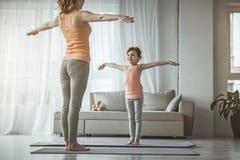 Счастливые девушка и мама делают простые тренировки спорта Стоковая Фотография