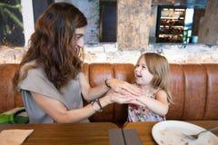 Счастливые девушка и мать в ресторане играя с руками Стоковая Фотография RF