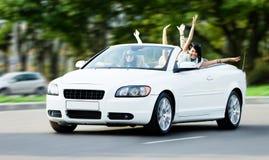 Счастливые девушки в автомобиле при outstretched рукоятки Стоковое фото RF