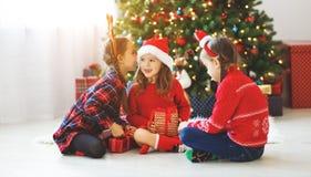 Счастливые девушки детей с подарками рождества около дерева в утре стоковые фото