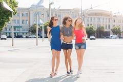 Счастливые девушки имея потеху пока идущ в городе Стоковые Изображения RF