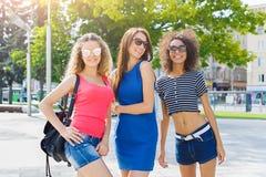 Счастливые девушки имея потеху пока идущ в городе Стоковые Изображения