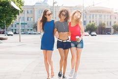 Счастливые девушки имея потеху пока идущ в городе Стоковая Фотография RF