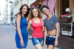 Счастливые девушки имея потеху пока идущ в городе Стоковое Изображение RF