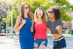 Счастливые девушки имея потеху пока идущ в городе Стоковая Фотография
