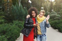 Счастливые девушки имея потеху пока идущ в парке Стоковая Фотография RF