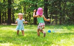 Счастливые девушки малыша играя в спринклере Стоковая Фотография