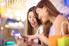Счастливые девушки наблюдая телефон в торговом центре Стоковое Изображение RF