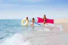 Счастливые девушки наслаждаясь летом на тропическом пляже Стоковые Изображения