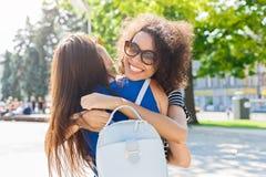 Счастливые девушки обнимая пока идущ в город Стоковое Фото