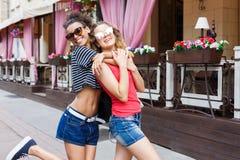 Счастливые девушки обнимая пока идущ в город Стоковые Изображения RF