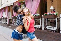 Счастливые девушки обнимая пока идущ в город Стоковое фото RF