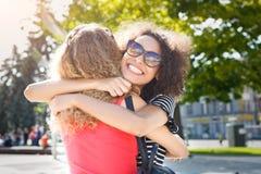 Счастливые девушки обнимая пока идущ в город Стоковые Изображения