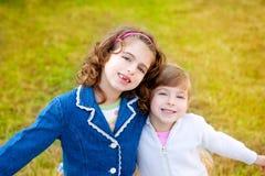 Счастливые девушки сестры в парке зимы засевают играть травой Стоковые Изображения RF