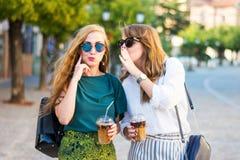 Счастливые девушки сплетни идя в город Стоковые Фото