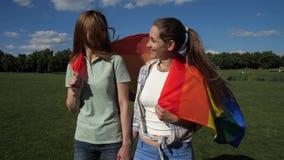 Счастливые девушки с флагом lgbt идя на лужайку видеоматериал