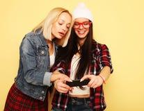 Счастливые девушки с smartphone над желтой предпосылкой Счастливая собственная личность Стоковые Фото