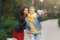 Счастливые девушки с smartphone outdoors в парке Стоковое Изображение
