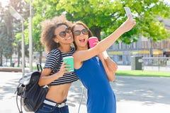 Счастливые девушки с smartphone outdoors в парке Стоковые Фотографии RF