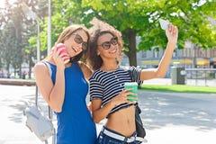 Счастливые девушки с smartphone outdoors в парке Стоковые Изображения RF