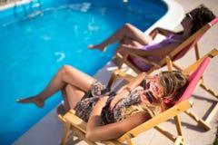 Счастливые девушки усмехаясь бассейном и наслаждаясь летом Стоковая Фотография
