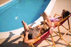 Счастливые девушки усмехаясь бассейном и наслаждаясь летом Стоковые Изображения RF
