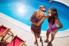Счастливые девушки усмехаясь бассейном и наслаждаясь летом Стоковая Фотография RF