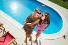 Счастливые девушки усмехаясь бассейном и наслаждаясь летом Стоковое Изображение