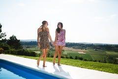 Счастливые девушки усмехаясь бассейном и наслаждаясь летом Стоковые Изображения