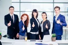 Счастливые деловые партнеры смотря камеру показывают большие пальцы руки вверх Стоковая Фотография RF