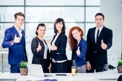Счастливые деловые партнеры смотря камеру показывают большие пальцы руки вверх Стоковые Изображения RF