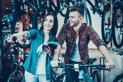 Счастливые детеныши соединяют говорить пока выберите новый велосипед стоковое фото
